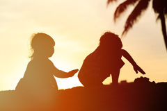 Konturer av två ungar spelar på solnedgångstranden Royaltyfri Bild