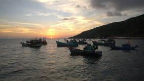 Konturer av vietnamesiska traditionella fiskebåtar som svävar på det sceniska blåa havet mot guld- solnedgång arkivfilmer