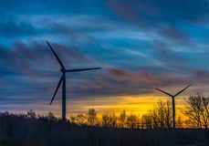 Konturer av vindturbiner med en härlig solnedgång Arkivfoto
