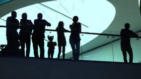 Konturer av vuxna människor och barn som står nära den glas- ledstången i modern byggnad video 4K lager videofilmer