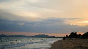 Konturerna av folk fiskar på stranden i aftonen och bergen arkivfilmer