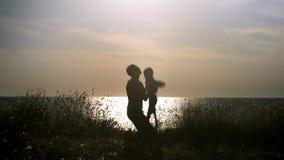 Konturfader och son som har gyckel på stranden på solnedgången, farsa som kastar den unga pojken upp in i luften lager videofilmer