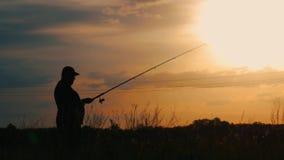 Konturfiskare som kastar metspöet i floden på bakgrundsaftonsolnedgång Härlig aftonsolnedgång under fiske stock video