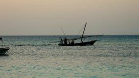 Konturfiskebåt med fiskare som seglar på havet i afton lager videofilmer