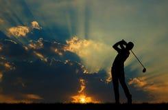 Konturgolfare som spelar golf på den härliga solnedgången Royaltyfria Bilder