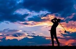 Konturgolfare som spelar golf på den härliga solnedgången Royaltyfri Bild