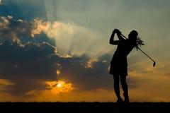 Konturgolfare som spelar golf på den härliga solnedgången Arkivbilder