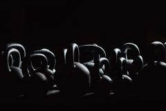 Konturhantel för viktutbildning i idrottshall Svarta kettlebells 24kg weightliftingen Fotografering för Bildbyråer