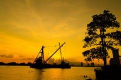 Konturkonstruktionsplats som svävar över floden med reflexion på solnedgång Arkivbild