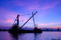Konturkonstruktionsplats som svävar över floden med reflexion på solnedgång Royaltyfri Fotografi