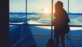 Konturkvinnalopp med bagage som ser utan fönstret på flygplatsen arkivbild