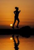 Konturkvinnaspring mot orange solnedgång Arkivfoton