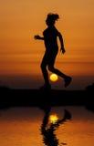 Konturkvinnaspring mot orange solnedgång Arkivbilder