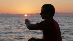 Konturman med smartwatch förestående på solnedgångstranden Han trycker på de smarta klockorna och kontrollerar meddelandet Solen  arkivfilmer