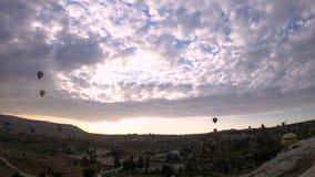 Konturmassor av ballonger för varm luft som flyger över dalar i Goreme, Turkiet Timelapse med små moln på himlen stock video
