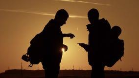 Konturn av anseendet för två man på överkanten av berget med ryggsäckar och bruk ringer för navigering Livsstil lopp stock video