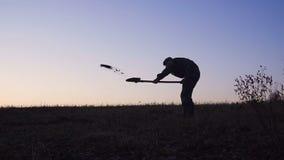 Konturn av arbetarna som skyfflar jorden med en spade i aftonen lager videofilmer