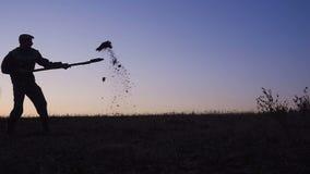 Konturn av arbetarna som skyfflar jorden med en spade i aftonen arkivfilmer