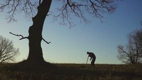 Konturn av arbetarna som skyfflar jorden med en spade i aftonen stock video