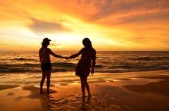 Konturn av barn kopplar ihop förälskat på stranden när solnedgången Royaltyfri Fotografi
