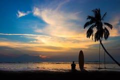 Konturn av bränningmannen sitter med en surfingbräda på stranden Fotografering för Bildbyråer