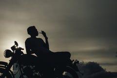 Konturn av cyklistmansammanträde röker med hans moped bredvid den naturliga sjön och härligt och att tycka om frihet och aktivlif Royaltyfri Bild
