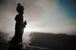 Konturn av den arabiska mannen står bara, i öknen och att hålla ögonen på solnedgången med moln av dimma Östlig saga Royaltyfri Fotografi