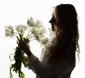Konturn av den härliga lockiga flickan med våren blommar tulpan på en vit bakgrund Arkivbild