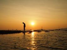 Konturn av den ledsna unga mannen som dejectedly står, vänder tillbaka till solen på havsstranden med härlig himmelsolnedgångbakg Arkivfoton