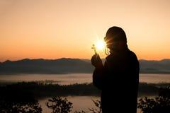 Konturn av den mänskliga handen som rymmer korset, bakgrunden, är soluppgången arkivfoton