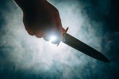 Konturn av den manliga handen rymmer kniven, manmördare- eller galningbegreppet royaltyfri bild