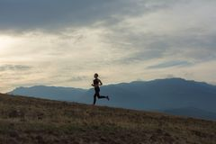 Konturn av den slanka flickan joggar i dimmiga berg royaltyfria foton
