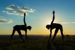 Konturn av den sportiga mannen och kvinnan som gör triangeln, poserar Royaltyfria Bilder