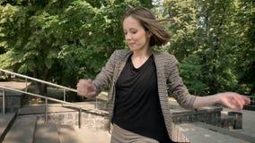 Konturn av den unga gulliga flickan dansar på trappa parkerar in i dag, i sommar, rörelsebegreppet, baksidasikten, sidosikt arkivfilmer