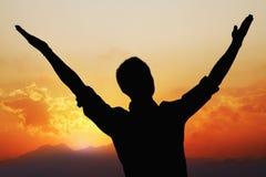 Konturn av den unga mannen med armar lyftte med en härligt solnedgång och landskap i bakgrunden royaltyfri bild