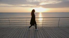 Konturn av den unga stilfulla affärskvinnan med lockigt hår promenerar träinvallningen nära havet eller havet lager videofilmer