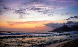 Konturn av det Dois Irmaos berget, härlig himmel av solnedgången och reflexionen av himlen i Atlantic Ocean på Ipanema sätter på  arkivbilder