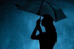 Konturn av diagramet av en ung flicka med ett paraply i regnet, en ung kvinna är lycklig till droppar av vatten, begreppsväder arkivfoton