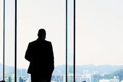 Konturn av en kompetent vd för asiatisk man av det lyckade företaget ser in i det stora fönstret på affärsområde i Hong Kong royaltyfri fotografi