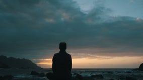 Konturn av en kvinna som sitter på, vaggar på solnedgången observera havvågor på den Benijo stranden i Tenerife, kanariefågelöar arkivfilmer