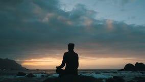 Konturn av en kvinna som sitter p?, vaggar p? solnedg?ngen observera havv?gor p? den Benijo stranden i Tenerife, kanarief?gel?ar lager videofilmer