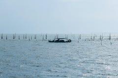 Konturn av en liten fiskebåt i havet royaltyfria bilder