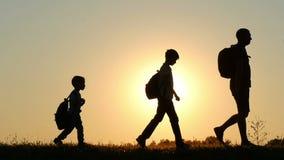 Konturn av en lycklig familj av turister går med ryggsäckar, under solnedgång Farsan och två söner följer sig lager videofilmer