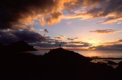 Konturn av en man i det naturliga landskapet av en solnedgång över arkivbilder