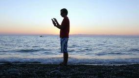 Konturn av en man på solnedgången passerar längs stranden med en minnestavladator Han stoppar, kontrollerar meddelandet och flytt stock video