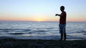 Konturn av en man på solnedgången passerar längs stranden med en smart klocka Han stoppar, kontrollerar meddelandet på smartwatch stock video