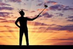 Konturn av en narcissistisk och självisk man med en krona på hans huvud, gör selfie på telefonen royaltyfri fotografi