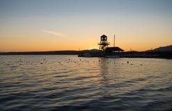Konturn av en sjöpir och shoreline på solnedgången arkivfoto