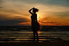 Konturn av en slank brunettflicka i frodig kort kjol som är stan royaltyfri fotografi