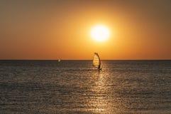 Konturn av en surfare på ett bräde under en segla fortskrider en lugna vattenyttersida på solnedgången över havet, horisont arkivbilder
